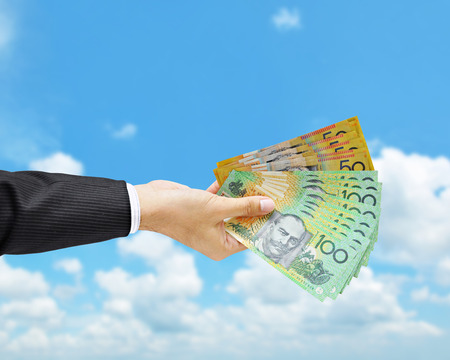 inducement: Money - hand holding Australian dollar (AUD) banknotes on blue sky background Stock Photo