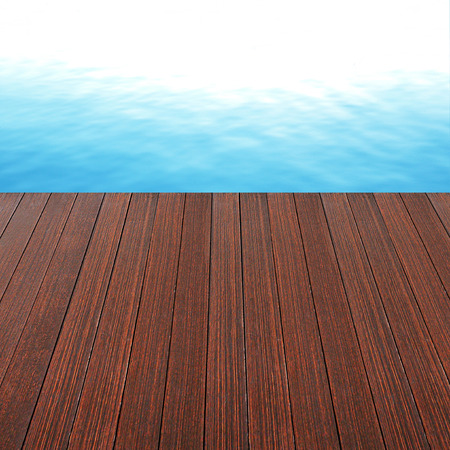 pool deck: Wood plank as a pier on blue still water background