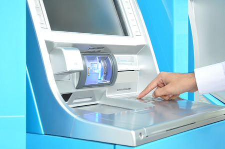 automatic teller machine bank: ATM  or Automated Teller Machine   with hand pressing on the keypad