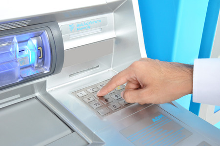 automated teller: ATM  or Automated Teller Machine   with hand pressing on the keypad
