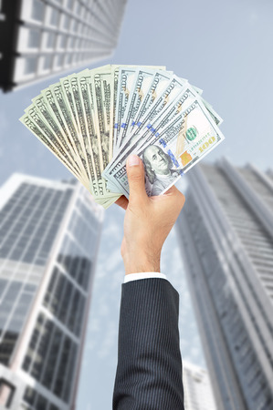 inducement: Hand holding money - United States Dollars (or USD) - on building background