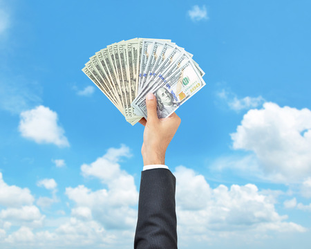 to raise: Money - hand holding United States dollar banknotes on blue sky background Stock Photo