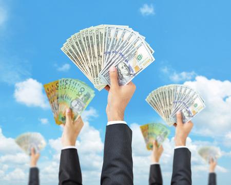 Hands holding money in multi currencies - money raising, funding & consumerism concept photo