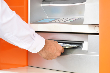 withdraw: Hand taking (withdraw) money from ATM