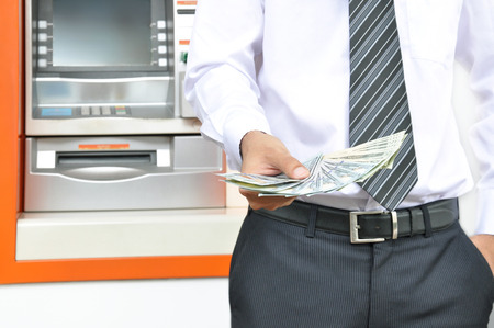 Money - a man holding US dollar banknotes in front of ATM background photo