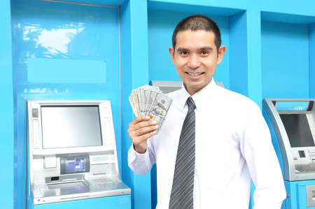 Asian businessman holding money - United States Dollars (USD) - in front of ATM machines Stock Photo
