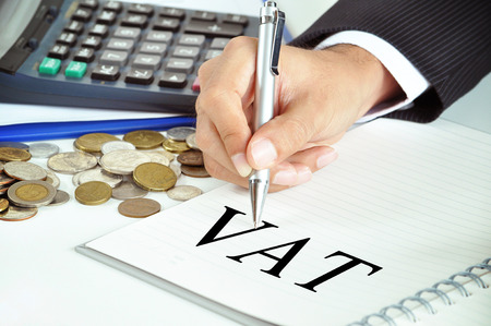 vat: Hand with pen pointing to VAT (or Value Added Tax) sign on the paper - commercial & taxation concept Stock Photo