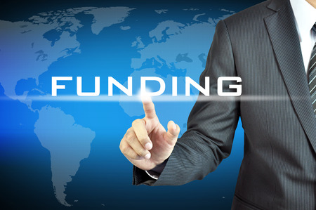 grants: Businessman hand touching FUNDING sign on virtual screen