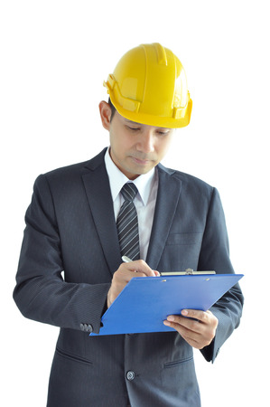 asian architect: Architect or engineer - Asian man wearing suit & hardhat writing on clipboard Stock Photo