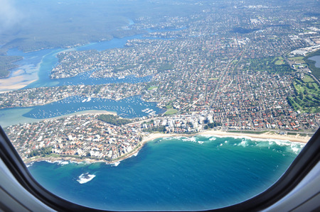 landscape: Aerial view of the city near seacoast from window of the airplane