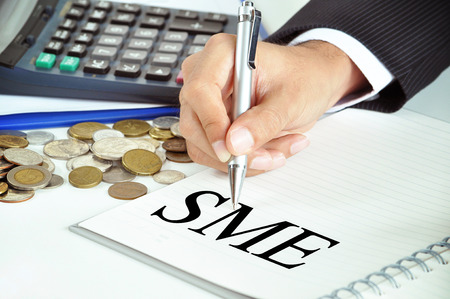 medium: Hand with pen pointing to SME (or small and medium enterprises) sign on the paper Stock Photo
