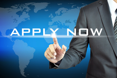 Businessman hand touching APPLY NOW word on virtual screen photo