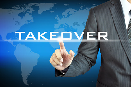 takeover: Businessman hand touching TAKEOVER word on virtual screen - business abstract