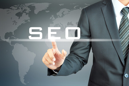 seo concept: Businessman hand touching SEO (or Search Engine Optimization) sign on virtual screen - internet & online marketing concept Stock Photo
