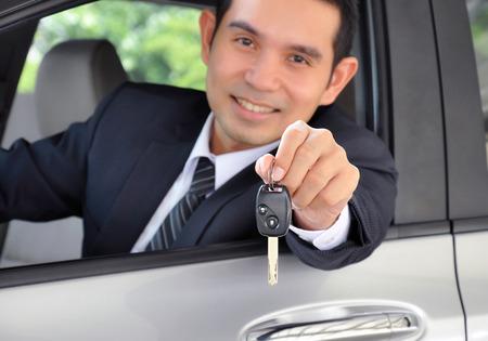 Asian businessman showing a car key - car sale & rental business concept photo