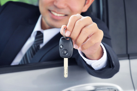 Businessman showing a car key - car sale & rental business concept photo