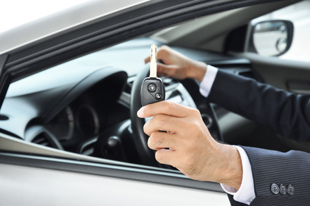 buy car: Hand holding a car key - car sale & rental business concept