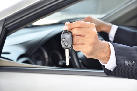 Hand holding a car key - car sale & rental business concept photo