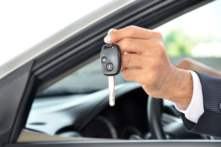 sell car: Hand holding a car key - car sale & rental business concept