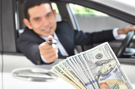 Businessman giving a car key exchanging with money - car ( auto) pawn concept photo