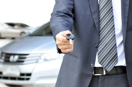 buy: Businessman giving a car key - car sale & rental business concept Stock Photo