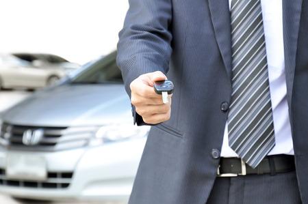 Geschäftsmann, der einen Autoschlüssel - Auto verkaufen und vermieten Geschäftskonzept Standard-Bild