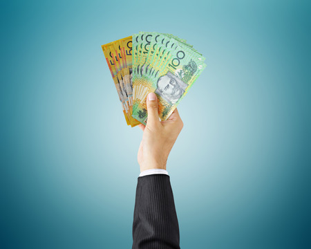 Hand holding money - Australian dollar (AUD) bills