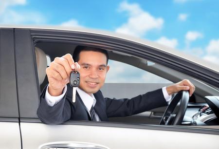 rental: Hombre de negocios asi�tico como conductor mostrando una llave del coche en el cielo azul de fondo - la venta de coches y alquiler de concepto de negocio Foto de archivo