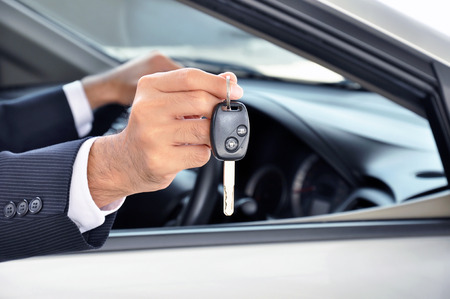 Hand holding a car key - car sale & rental business concept