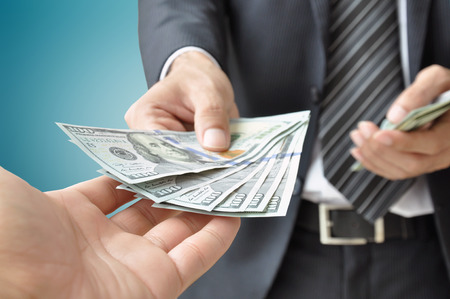 Hand receiving money from businessman - United States dollar (USD) bills photo