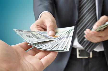 giving money: Hand receiving money from businessman - United States dollar (USD) bills