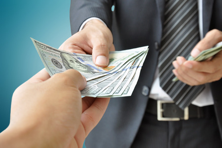 american money: Hand receiving money from businessman - United States dollar (USD) bills