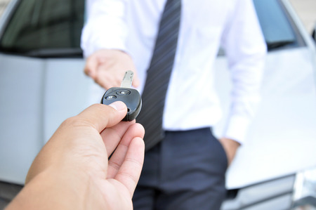 sell car: Hand giving a car key to another man - car sale & rental service concept Stock Photo