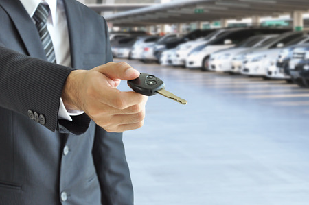Businessman hand giving a car key - car sale   rental business concept