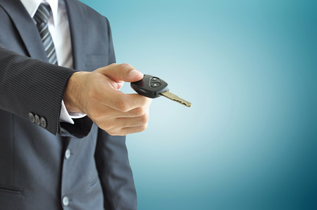 Leasing: Businessman hand giving a car key - car sale   rental business concept