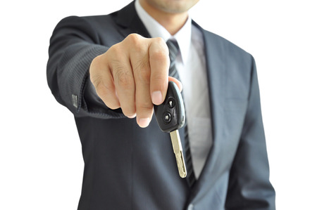 Businessman hand giving a car key - isolated on white background photo