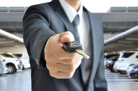 auto leasing: Businessman hand giving a car key - car sale   rental business concept