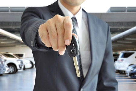 Businessman hand giving a car key - car sale   rental business concept photo
