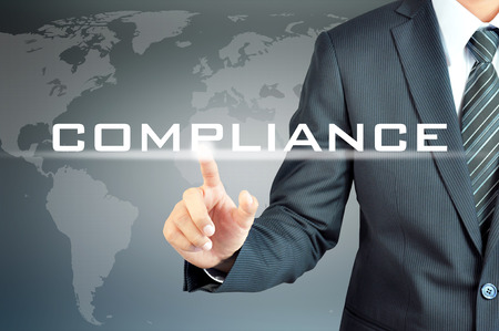 Businessman pointing to COMPLIANCE word on virtual screen