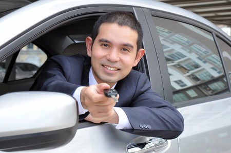 Asian businessman as a driver giving a car key - car sale & rental business concept photo