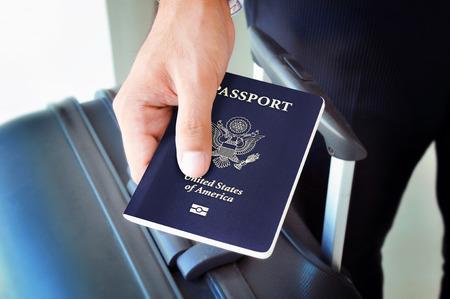 pasaporte: Mano que sostiene el pasaporte de EE.UU.