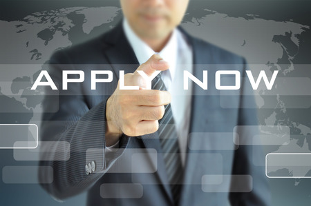 Businessman hand pointing to APPLY NOW on virtual screen photo