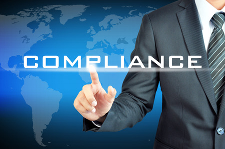 compliant: Businessman pointing to COMPLIANCE word on virtual screen