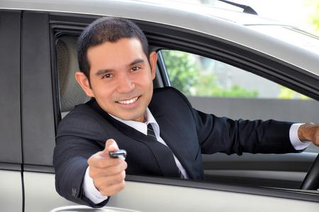 Asian businessman as a driver giving a car key - car sale & rental business concept photo