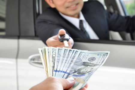 Businessman giving a car key exchanging with money - car ( auto) pawn concept