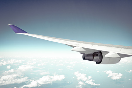 Airplane wing on blue sky background - retro style lighting effect