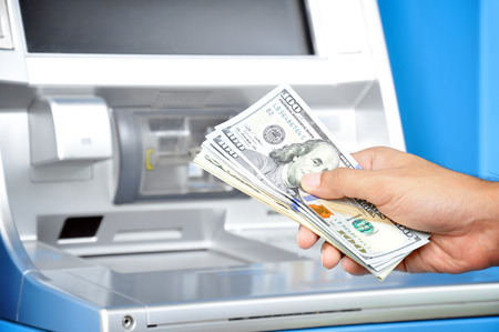 automatic teller machine bank: Hand holding money United States dollar (USD) bills in front of ATM Stock Photo