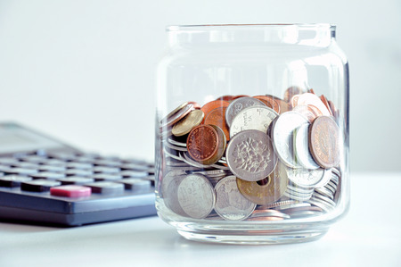 Coins in the glass jar (mixed Asian currencies) - saving concept photo