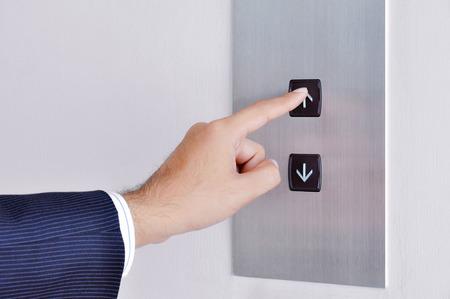 実業家の手サインを起こっているリフト コントロール パネルに触れる 写真素材