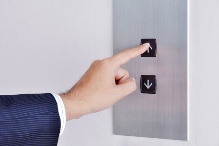 Tocar la mano de negocios que va encima de la muestra en el panel de control de elevación Foto de archivo - 32049996